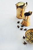 Cardamom capsules, anise stars and brass jugs