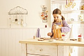 A girl decorating gingerbread with sugar strands