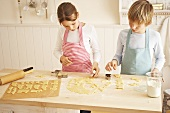 Children cutting out biscuits
