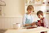 Children making chocolate Spritzgebäck (squirted biscuits)