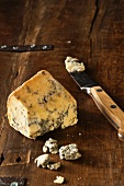A piece of Stilton with a knife on a wooden surface