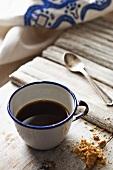Schwarzer Kaffee in Emailtasse, daneben Kekskrümel