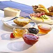 Breakfast with jam, meat, cheese and a basket of bread rolls