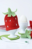 A strawberry-shaped egg cosy