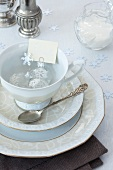 Coffee crockery with a name card and Christmas baubles