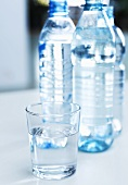 Glass of water and three bottles of water in background