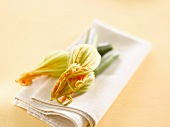 Three courgette flowers on a fabric napkin