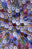 Bottle caps from different beers on blue background