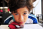 Boy sitting in restaurant waiting impatiently for food