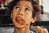 Boy eating chicken satay