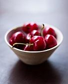 Several cherries in ceramic bowl