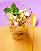 Fruit salad with raisins and mint in glass