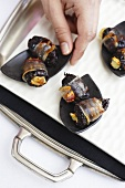 Hand reaching for bacon-wrapped prunes stuffed with goat's cheese
