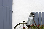 Milk can on old bicycle leaning on house wall