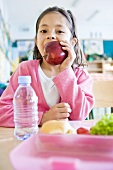 Girl eating an apple at school