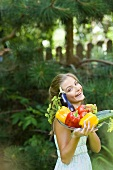 Woman holding plate of fresh vegetables in garden