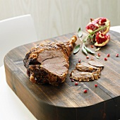 Partly carved leg of lamb with pomegranate seeds, chopping board