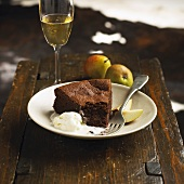 A piece of chocolate cake with ice cream and pear wedges