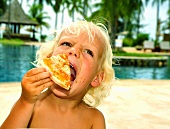 Child eating a slice of pizza