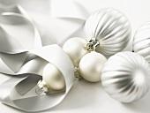 Silberfarbene Christbaumkugeln und Geschenkband