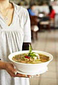 Woman carrying a bowl of pho (Beef and rice noodle soup)