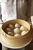 Woman with dim sum in bamboo steamer