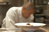 Chef plating a dish in a kitchen