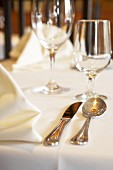 Fabric napkins, silver cutlery and glasses on tablecloth