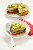 Potato cake with layers of spinach & peppers, spring onions