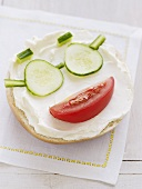 Bagel topped with cream cheese, tomato & cucumber (face)