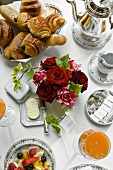 Pastries, coffee pot, roses, juice & fruit salad on breakfast table