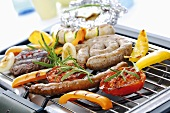 Meat, sausages and vegetables on grill