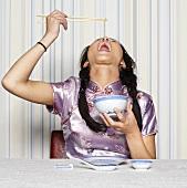 Asiatische Frau isst mit Essstäbchen
