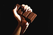 Female hand holding melting chocolate bar, close-up