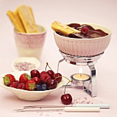 Chocolate fondue with sponge fingers and fruit
