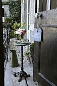 Blick durch geöffnete Tür auf schmalen Balkon mit kleinem rundem Tisch