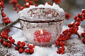 Ice bowl with candle and holly berries