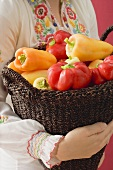 Woman holding basket of peppers (Hungary)