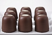Nine chocolate marshmallows on a platter