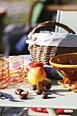 Esskastanien und Äpfel auf einem Gartentisch