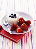 Heidelbeerjoghurt und Erdbeeren auf Notizbuch