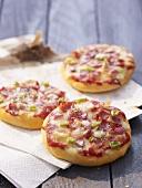Three small ham and spring onion pizzas