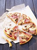Ham and mushroom pizza, cut into pieces
