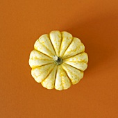 White pumpkin on brown background (overhead view)