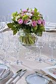 Vase of spring flowers on table laid for special occasion