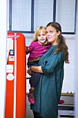 Mother holding small daughter beside refrigerator