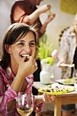 Frau isst Fingerfood auf einer Party