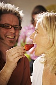 Couple with strawberry at a party