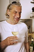 Grey-haired man drinking white wine