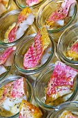 Red mullet fillets in glasses on a buffet